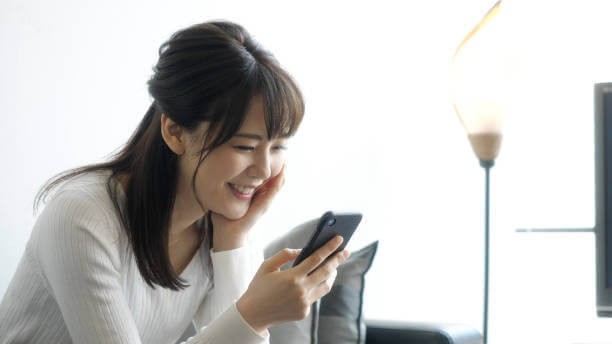 スマホを嬉しそうに見つめる女性|アインの集客マーケティングブログ