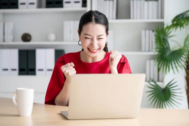 ガッツポーズをする女性とパソコン|アインの集客マーケティングブログ
